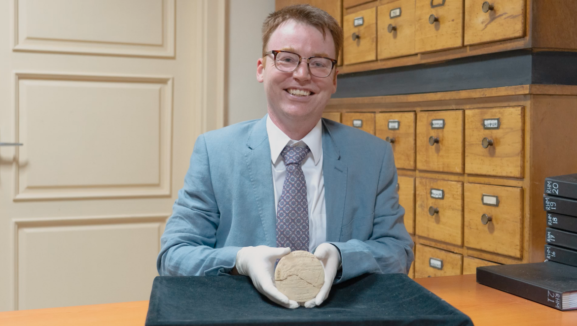 Dr Mansfield sits in a museum room proudly holding tablet Si.427 in white-gloved hands