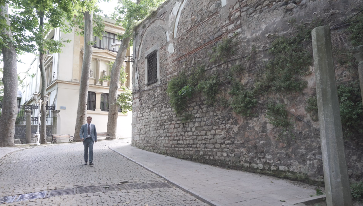 Dr Mansfield walks past a very old stone wall on a cobblestone street