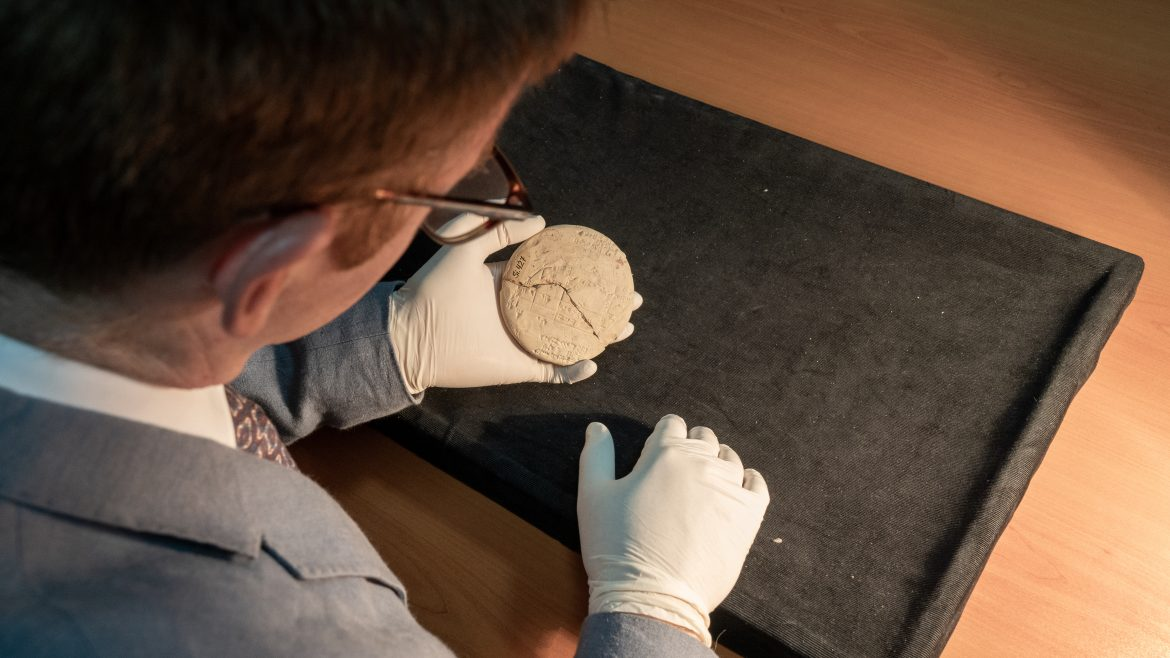 Dr Mansfield's gloved hands hold the disc-shaped tablet, about 20cm across, which is cracked and has markings on the flat sides